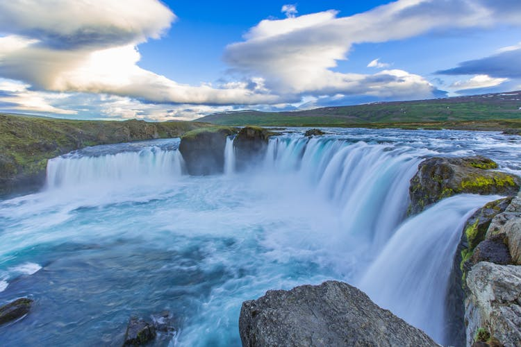 A rainbow forming over the beautiful Goðafoss waterfall in northern Iceland.