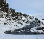 See dark lava rocks covered in white snow on your winter tour in Iceland.