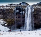 Visit the beautiful attractions of the South Coast before snowmobiling on a glacier on this minibus tour.