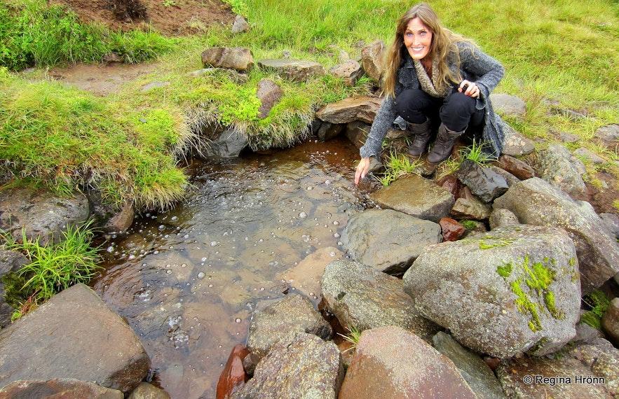Regína tasting the water at Rauðamelduölkelda mineral spring