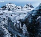 Sehe die dunklen, vulkanischen Streifen im weißen Eis des Sólheimajökull-Gletschers bei einer Gletscherwanderung.