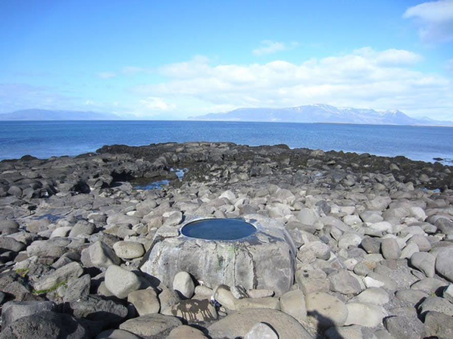 Kvika Foot Bath is found on Reykjavík's shoreline, with a mountain view