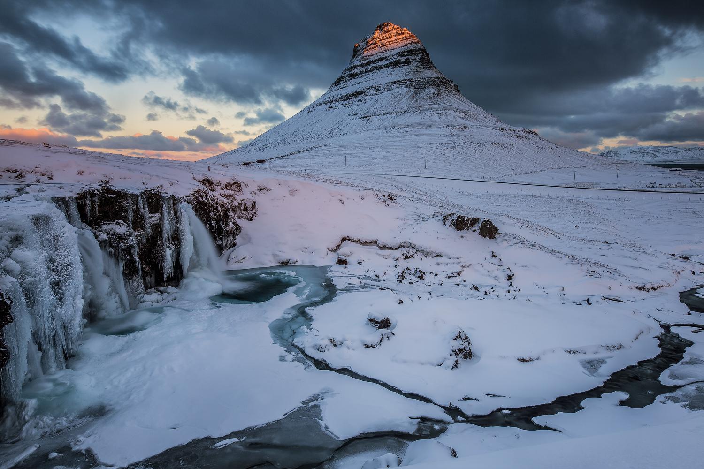 The dramatic Kirkjufell mountain towers over Grundarfjörður village on the Snæfellsnes Peninsula.