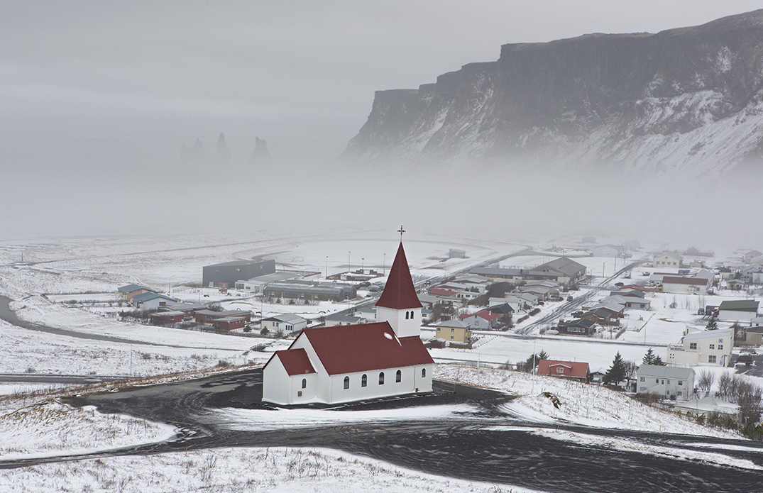 The charming town of Vík on the South Coast powdered in winter snow.
