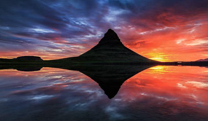 Mt. Kirkjufell on the Snæfellsnes peninsula reflecting on the water's still surface.