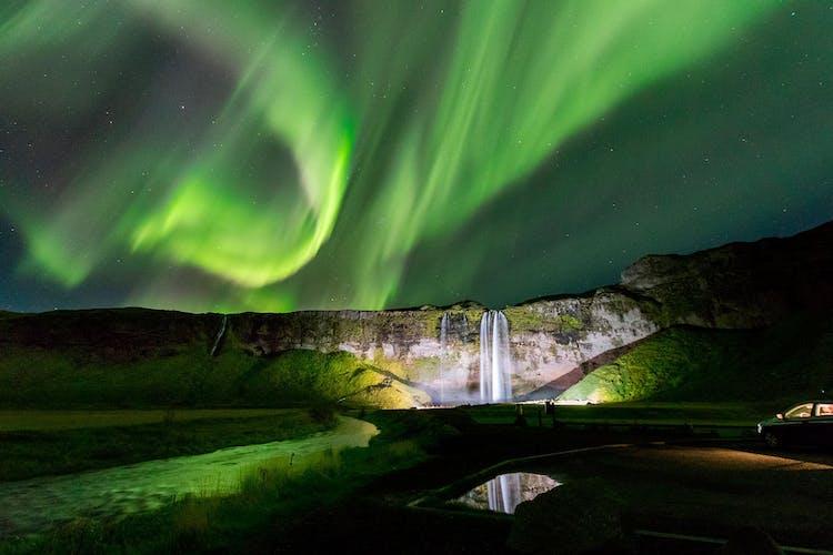 Les aurores boréales sur les cascades Seljalandsfoss de la côte sud.