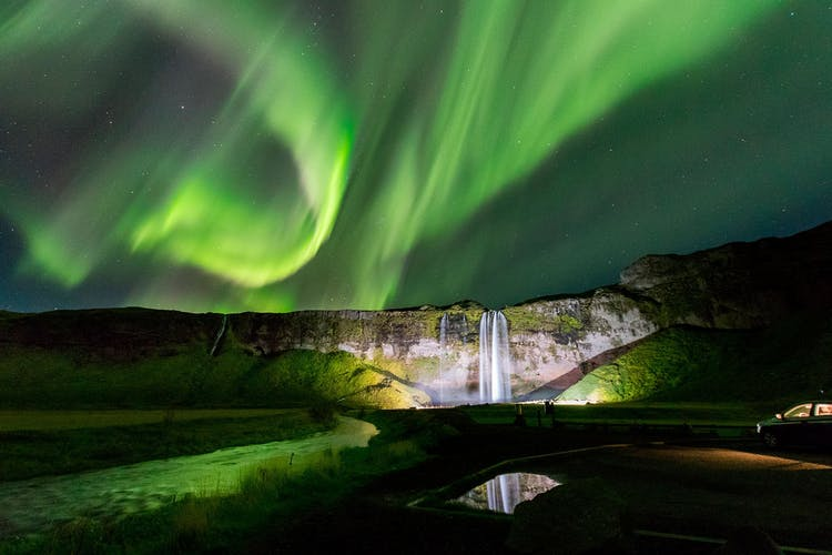 Zorza polarna porusza się jak tancerze na niebie nad wodospadem Seljalandsfoss na południowym wybrzeżu.