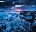 Icebergs scattered on a black sand beach near Jökulsárlón glacier lagoon.