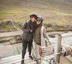 Two happy travellers pose for a picture on a wooden walkway in Iceland