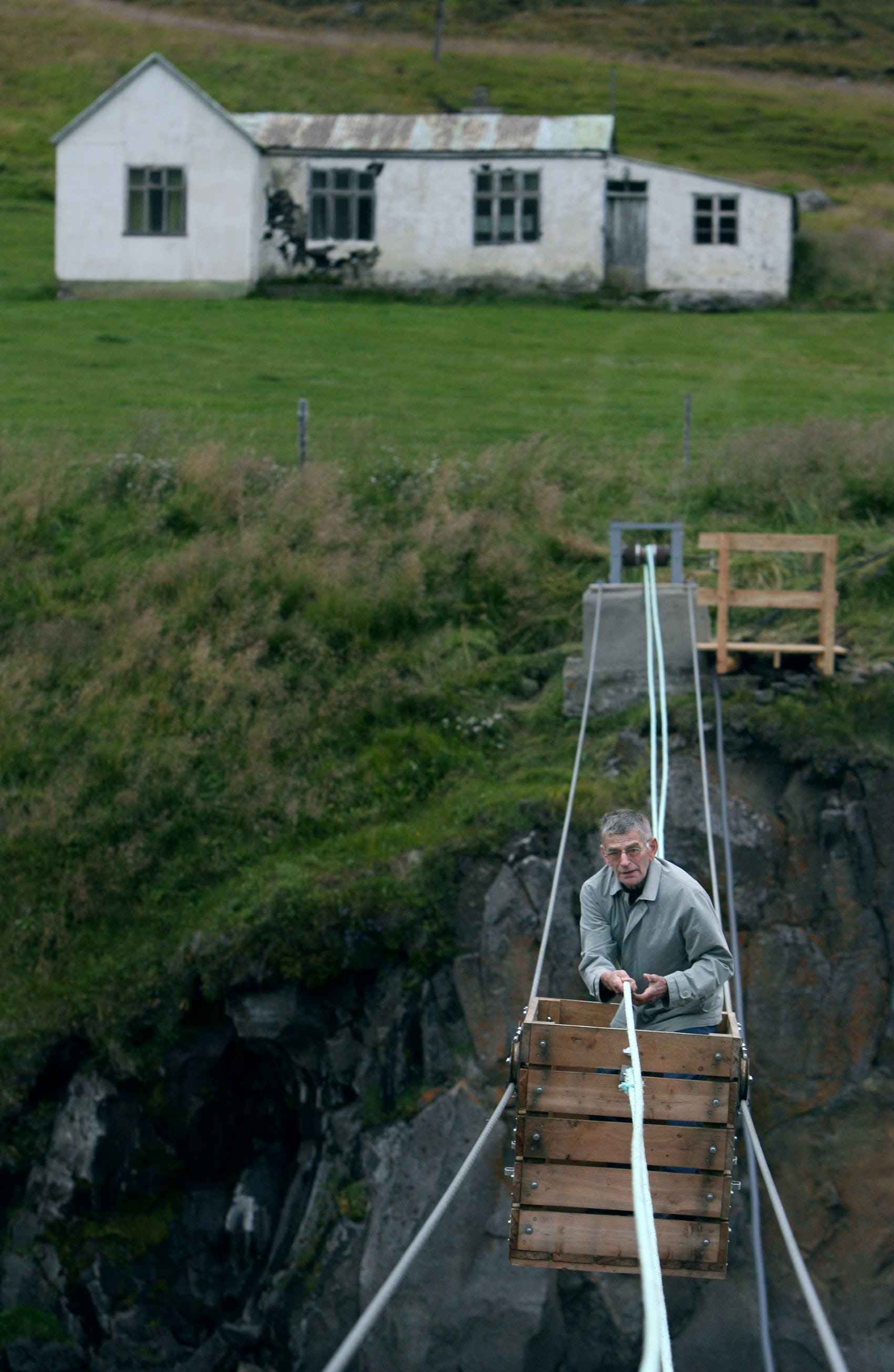 A traveller in Iceland is hand-pulled across a glacial river in a cableway cart
