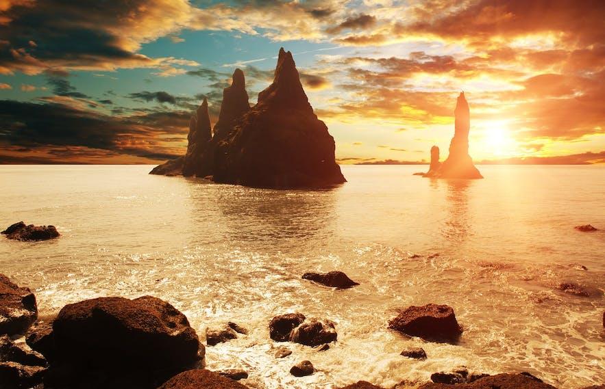 แสงอาทิตย์เที่ยงคืนอันอบอุ่นสาดส่องไปที่โขดทะเลเรนิสแดรงเกอร์