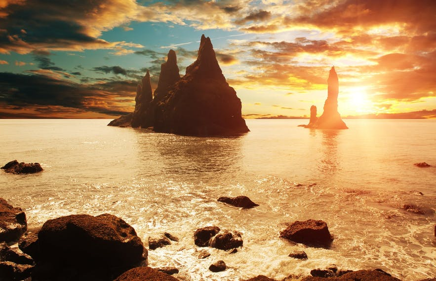The warm glow of the midnight sun bather the iconic Reynisdrangar seastacks.