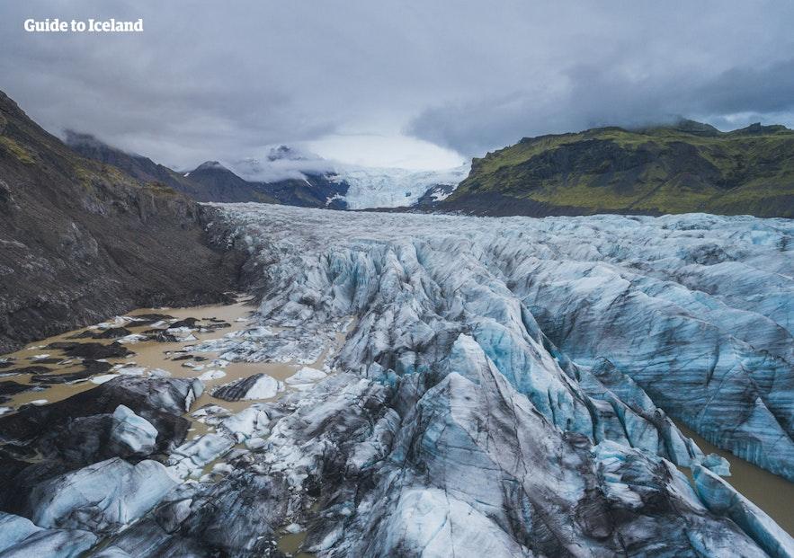 Svínafellsjökull on a cloudy day, still gleaming blue.