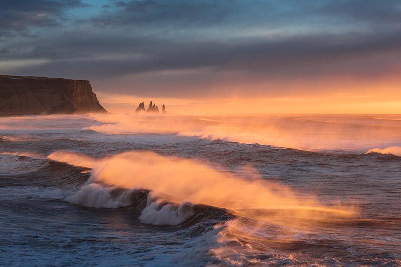 Die Felsnadeln Reynisdrangar in der Ferne, während das Meer ans Ufer prallt