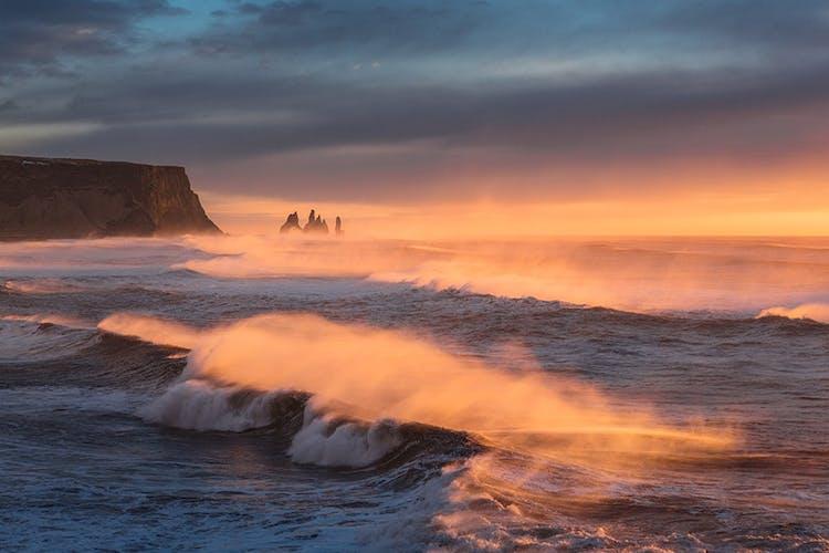 La roche Reynisdrangar s'empile au loin, lorsque la mer s'écrase sur le rivage.