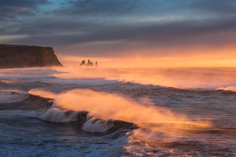 Reynisdrangar rock stacks in the far distance, as the sea crashes upon the shore.