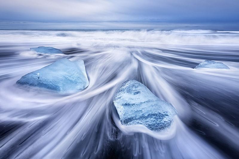 在冰岛南部钻石沙滩的墨黑色沙砾上的浮冰碎片