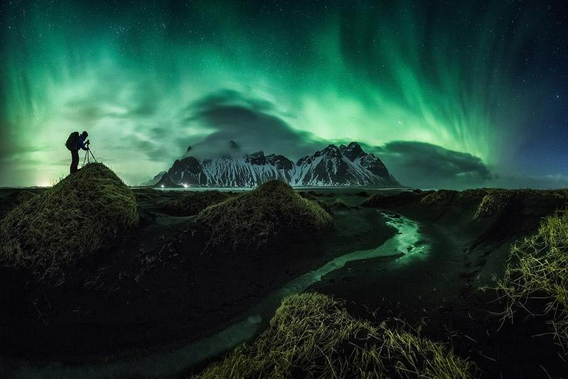 Vestrahorn pendant les mois d'hiver, avec des aurores dansant au-dessus.