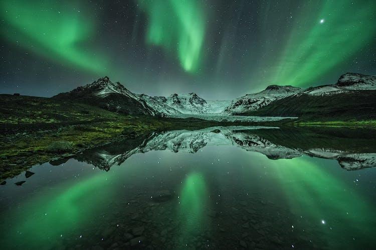 แสงออโรราสะท้อนเงาในทะเลสาบในคืนหน้าหนาว