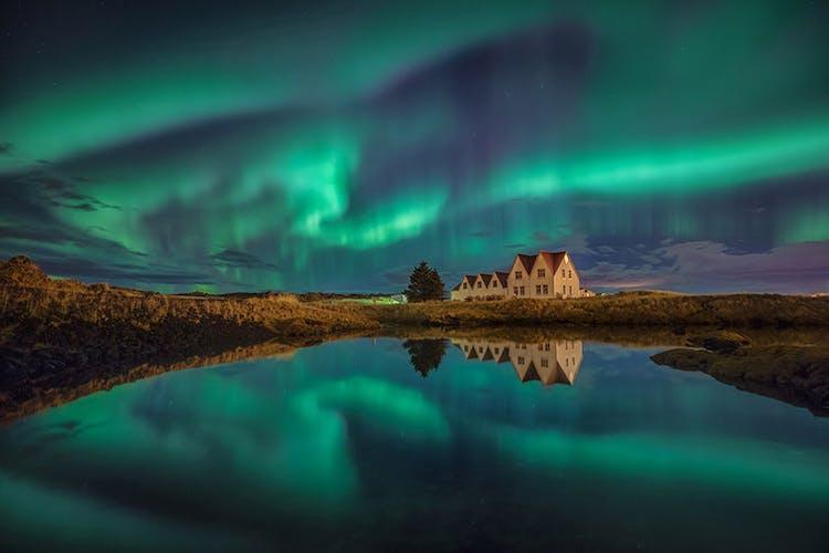 The houses at Þingvellir national park under the northern lights.