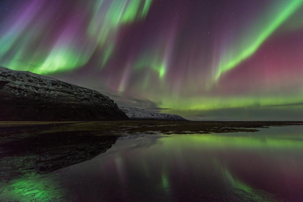 Les aurores boréales étincelantes dansent au-dessus des fjords de l'Est montagneux.