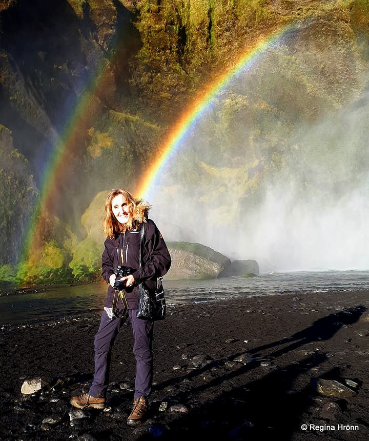Regína and a rainbow at Skógafoss Waterfall in South-Iceland