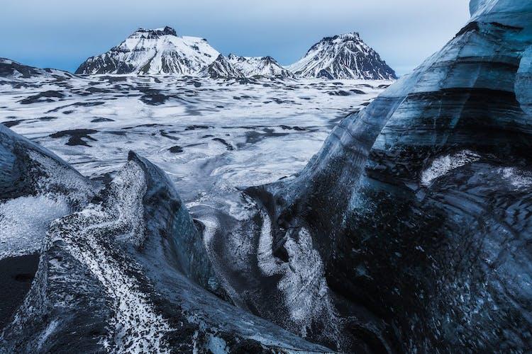 La glace blanche du glacier Mýrdalsjökull sur la côte sud est striée de rubans de cendres volcaniques noires.