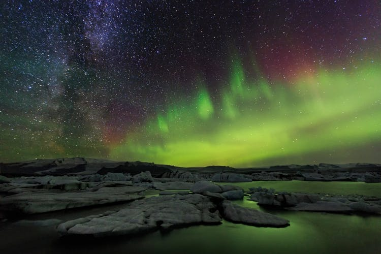 The Northern Lights reflect back to the sky on the still waters of Jökulsárlón glacier lagoon.