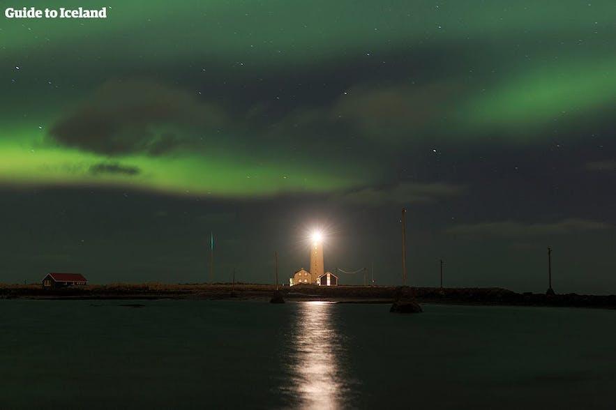 Аврора танцует над маяком в Исландии.