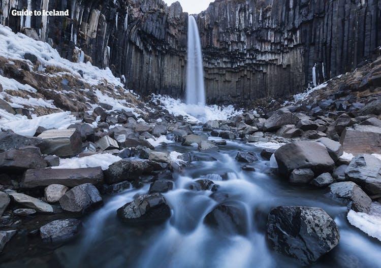 Sechseckige schwarze Säulen rahmen den hier im Winter abgebildeten Wasserfall Svartifoss in Südisland ein.