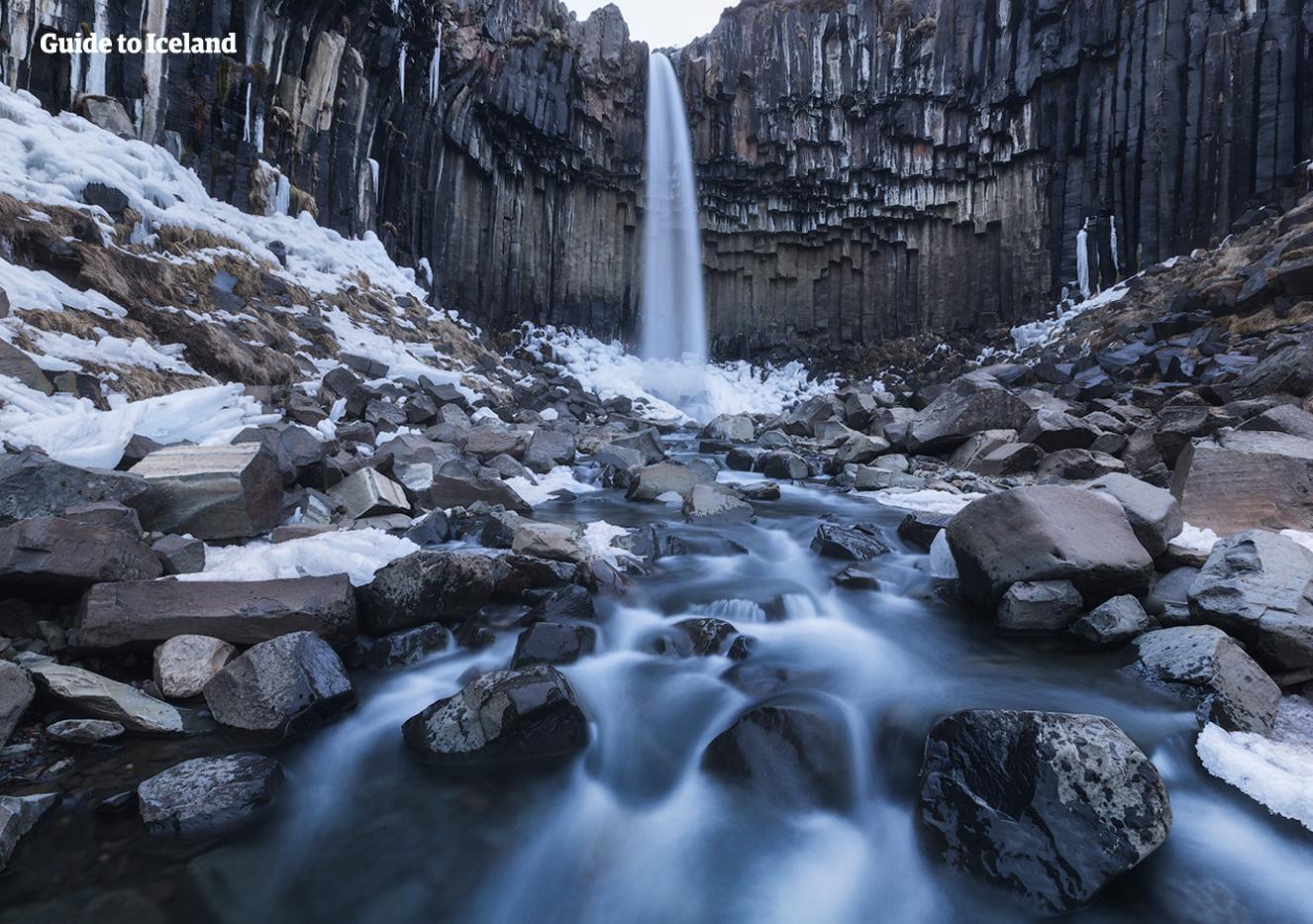 Sześciokątne czarne kolumny otaczają wodospad Svartifoss w południowej Islandii, przedstawiony tutaj zimą.