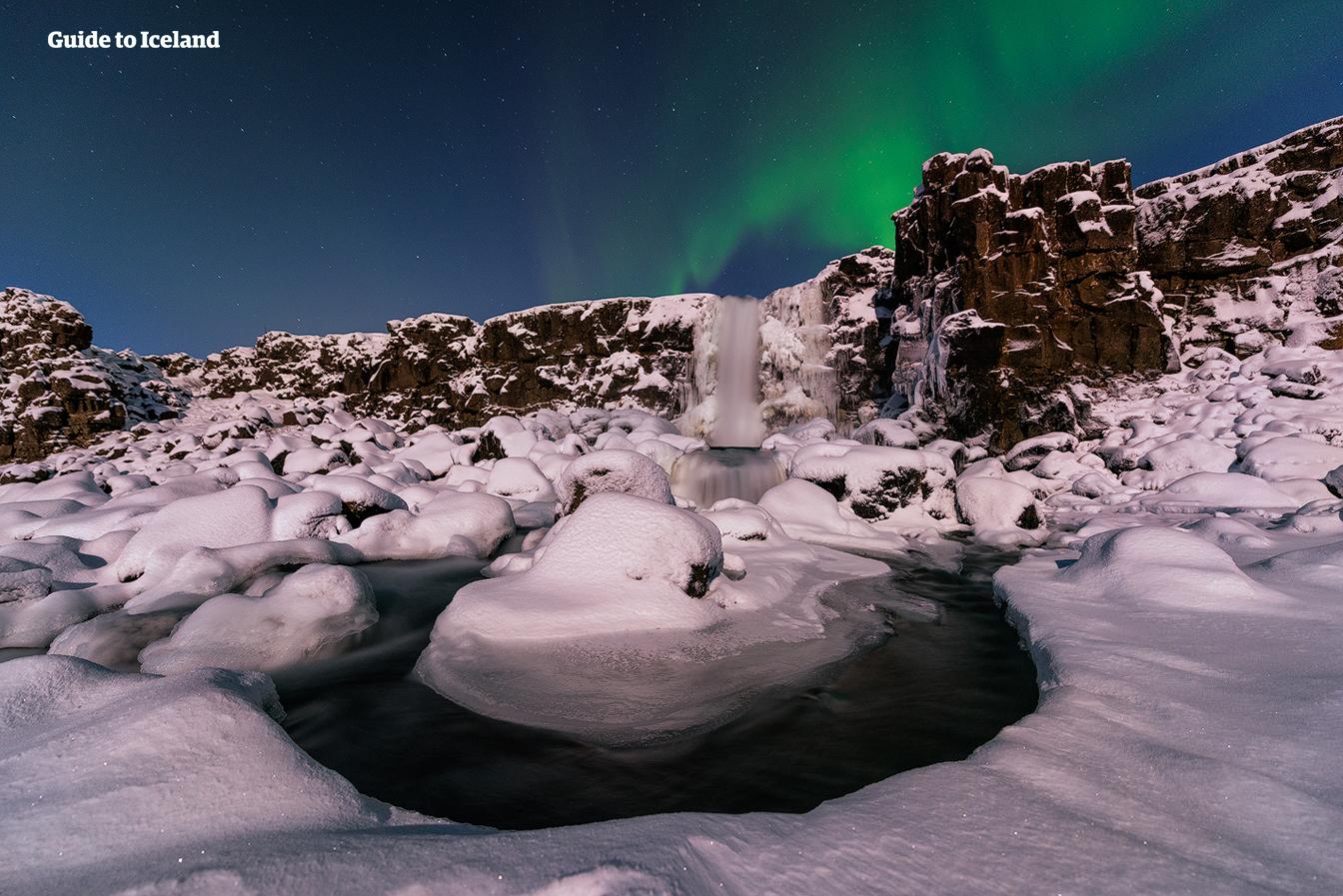 Öxarárfoss to wodospad w południowo-zachodniej Islandii, przedstawiony zimą pod zorzą polarną.