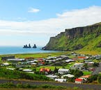 Vík Village, South Iceland, under Reynisfjall Mountain. Reynisdrangar sea stacks can be seen in the distance.