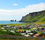 Village de Vík, sud de l'Islande, sous le mont Reynisfjall. On voit des piles de mer Reynisdranger au loin.