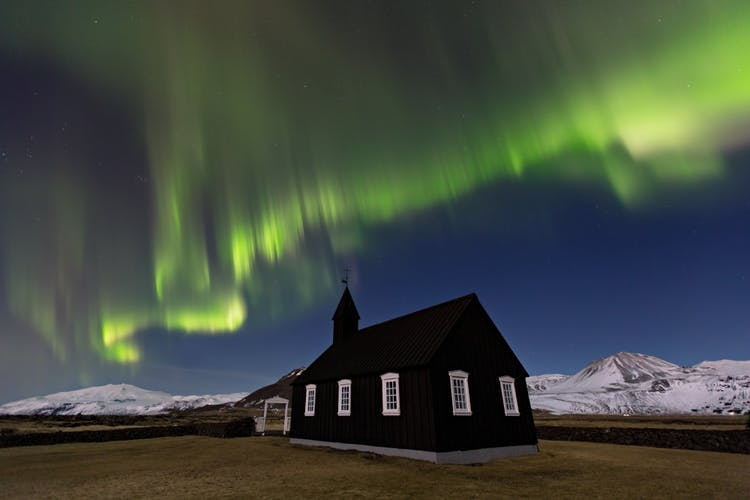 The photogenic Black Church at Búðir illuminated by the Northern Lights playing in the sky.