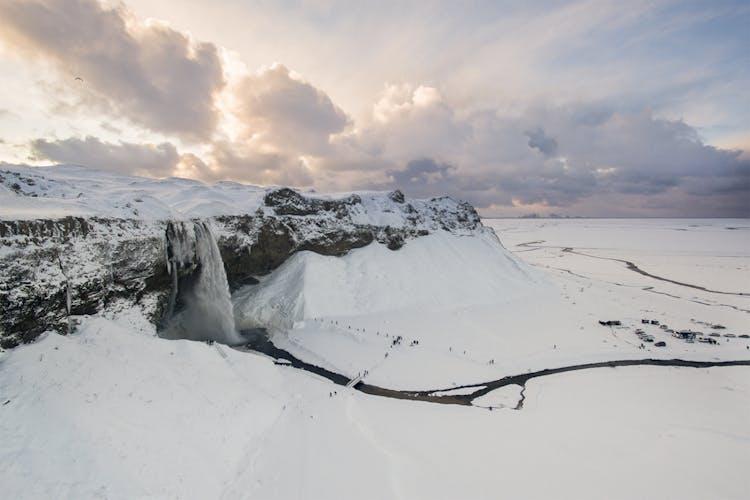 Seljalandsfoss waterfall in nestled in a frozen snowy blanket - it looks quite cosy!