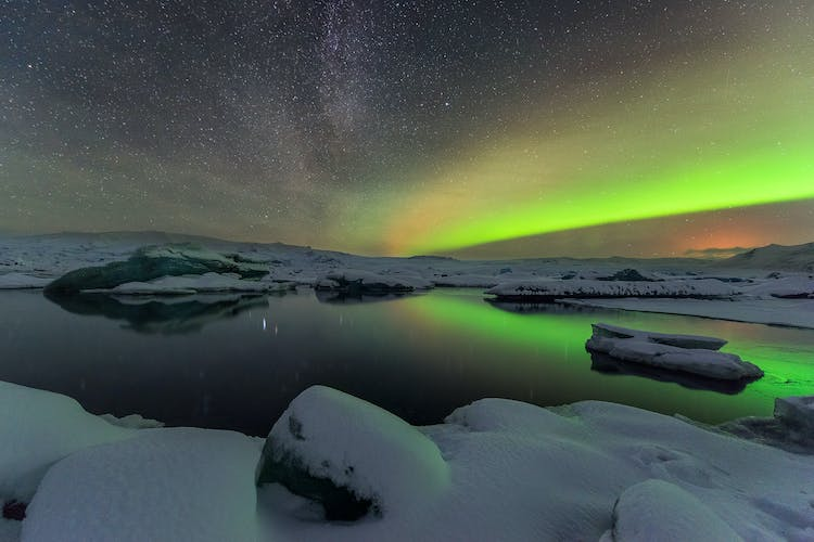 The gorgeous Northern Lights play across the sky covering the beautiful Jökulsárlón glacier lagoon.