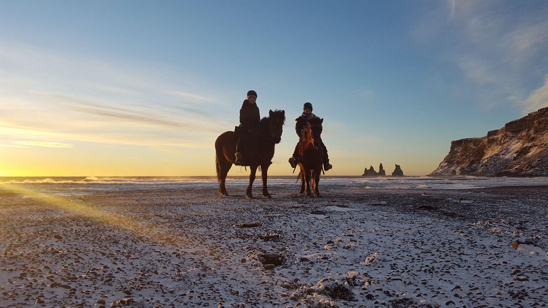 Reiter am schwarzen Strand bei Vík im frühen Winter, mit Reynisdrangar im Hintergrund.