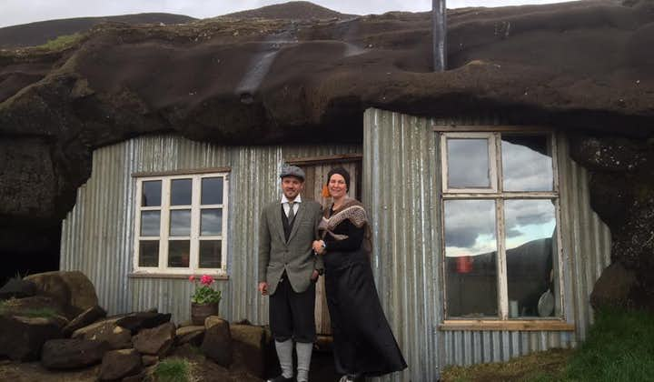 A couple in traditional clothing outside the Laugarvatnshellar cave house.