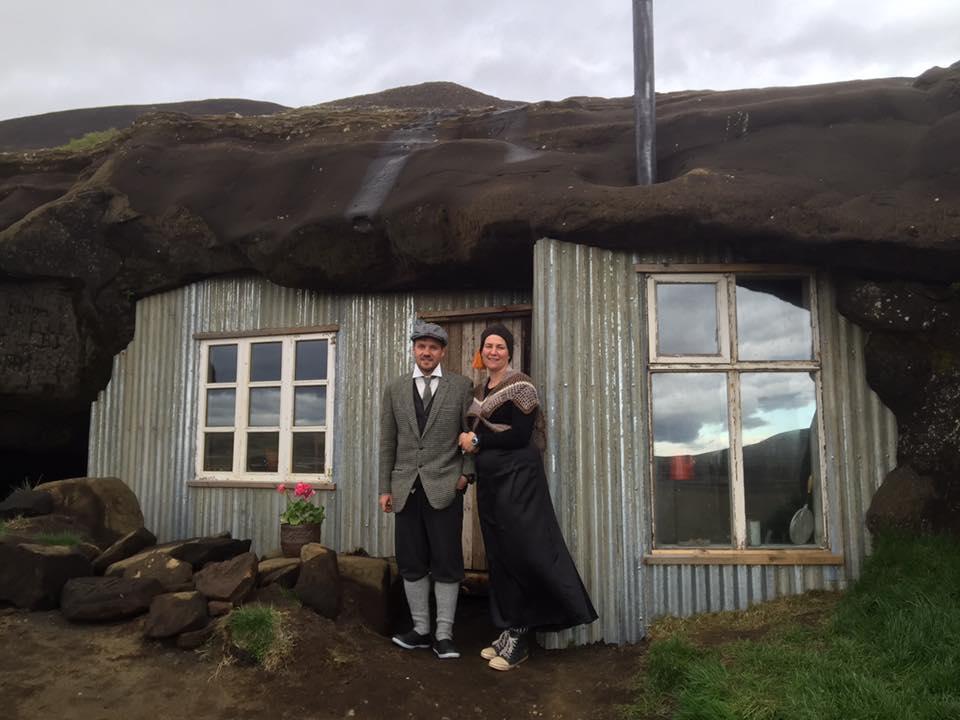 ロイガヴァトンスへトリル(Laugarvatnshellir)の洞窟の家と伝統衣装を着ているアイスランド人