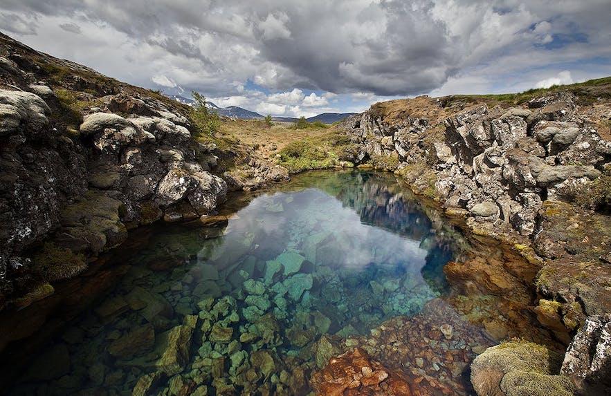 Bij de ingang van de Silfra-kloof kunnen bezoekers naar beneden kijken in het kristalheldere gletsjerwater.
