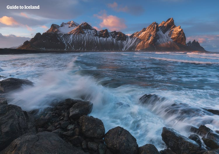 Vestrahorn mountain in East Iceland in front of the roaring waves of the Atlantic Ocean.