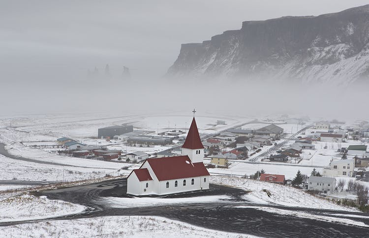 A fresh layer of snow powders the picturesque village on Vík on the South Coast of Iceland.