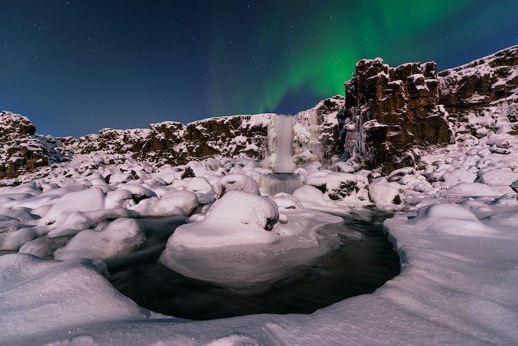 The Northern lights dance across the sky above Öxarárfoss waterfall in Þingvellir National Park.