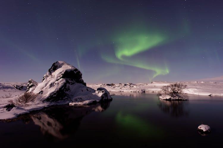 Die Aurora Borealis spiegelt sich im See Mývatn und den mit Wasser gefüllten Pseudokratern mit ihren schneebedeckten Felsstrukturen, die die Gegend im Norden Islands prägen.