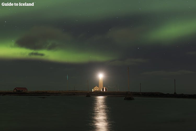 Grótta lighthouse in the greater Reykjavík area, striking an imposing wintery image on a northern lights filled night.