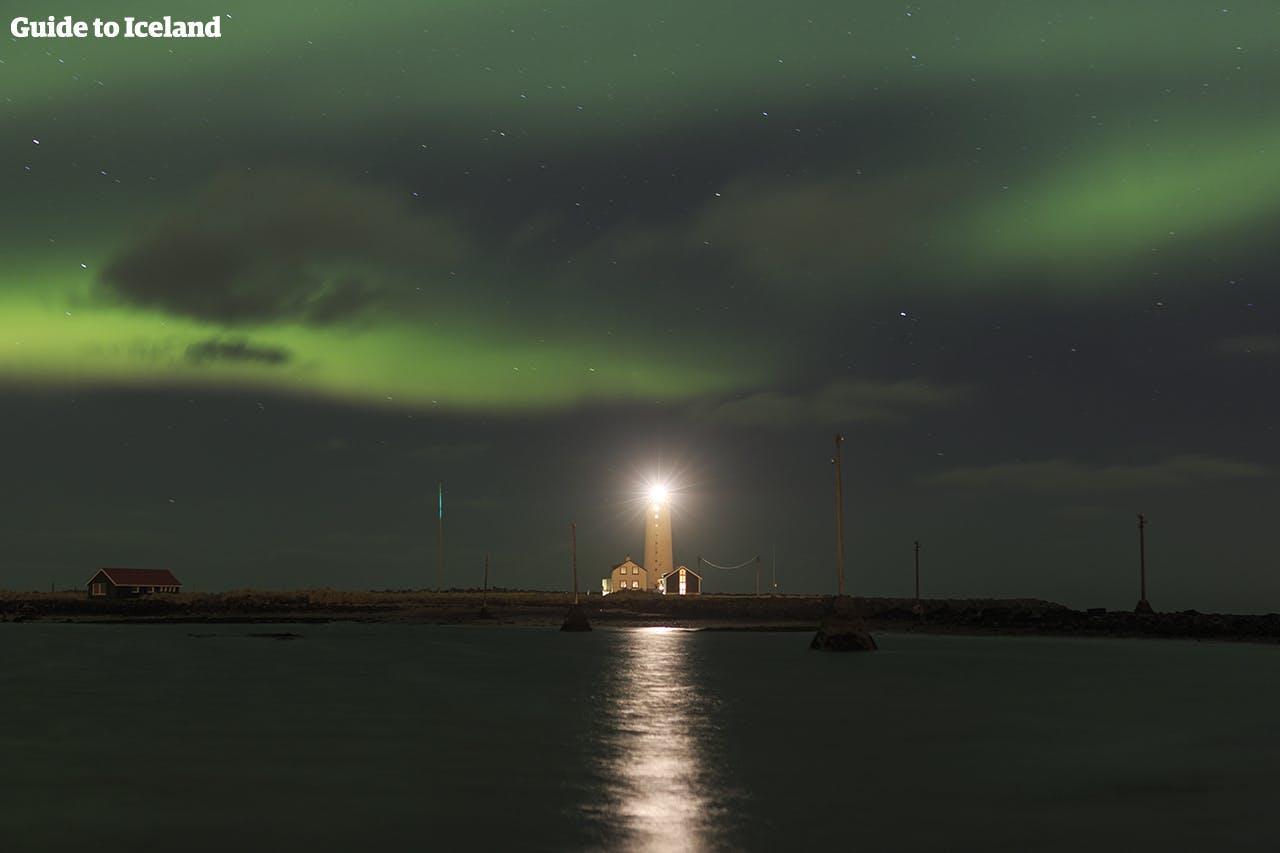 Latarnia morska Grótta w Reykjaviku z tańczącą nad nią zorzą polarną.