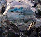Blick durch ein eisiges Fenster auf die gigantischen Eisberge, die ruhig in Richtung Ozean ziehen.