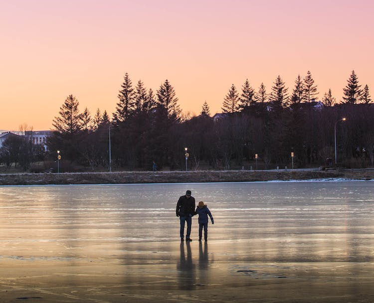 People walking over the frozen Reykjavík pond, Tjörnin, in the low light on a late winter afternoon.