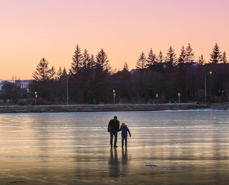 Personnes marchant sur l'étang gelé de Reykjavík, Tjörnin, dans la pénombre l'après-midi d'hiver.